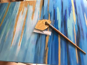 Applying gold leaf to painting